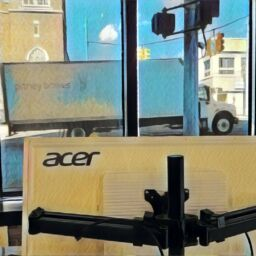 Office shot of an acer computer and semi-truck on the road
